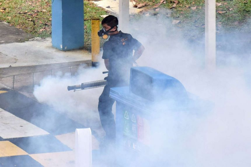 A worker fumigates an area against aedes mosquitoes which carry the dengue virus at a residential estate in Singapore on April 5, 2016.