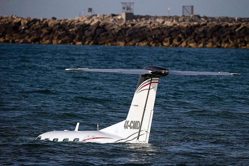 A light Israeli aircraft in the Mediterranean Sea off Tel Aviv's shore after an emergency landing on Sunday. The pilot crash-landed the plane after he failed to make an emergency landing at the Sde Dov Airport. A coast guard patrol rescued him and a
