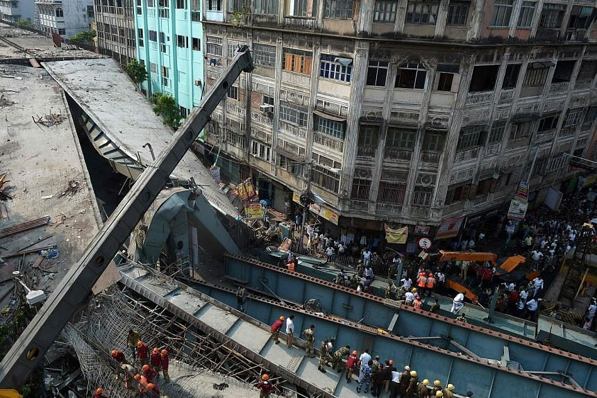 Rescuers and volunteers trying to free people trapped under the collapsed portion of the flyover in Kolkata last Thursday. In many of India's large cities, public works projects are launched by politicians for pre-election boosts and lose their urgen