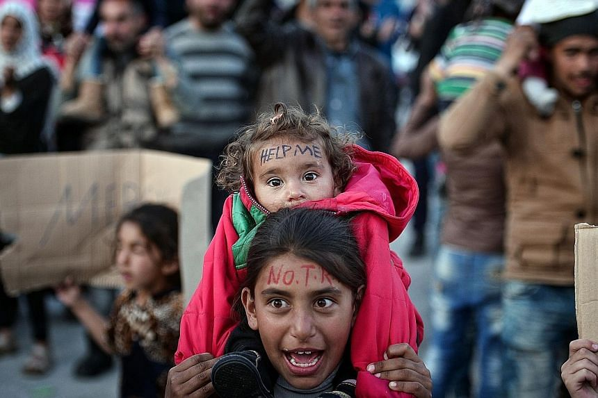 """People on the Greek island of Chios shouting """"No Turkey"""" in protest against an EU-Turkey deal on the return of refugees and migrants."""