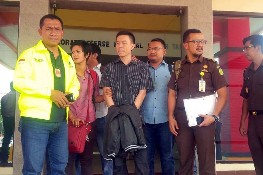 Singaporean Lim Yong Nam in black striped shirt (centre) leaving the Riau Islands province's detective office in Batam, flanked by a policewoman (in red shirt), prosecutors (dark brown uniform) and Interpol officers. He was heading to Hang Nadim inte
