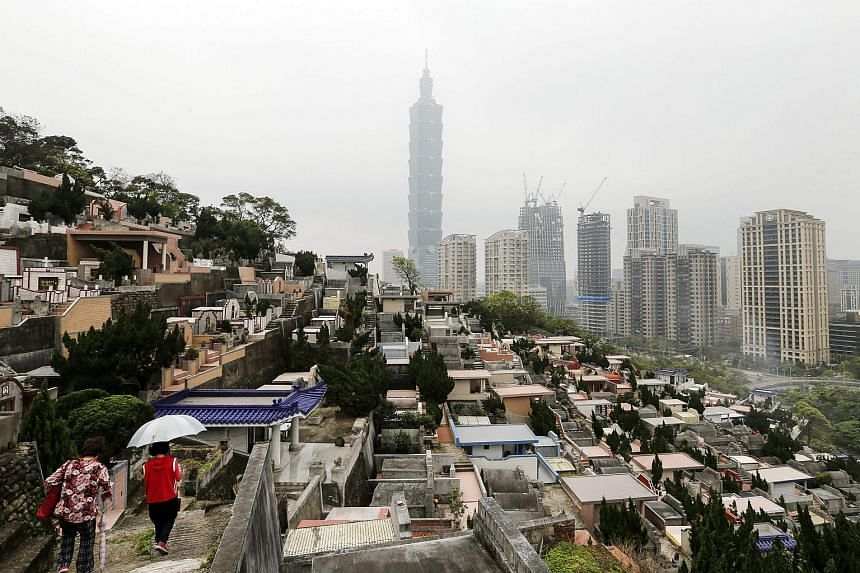 Two women visit their deceased relatives to mark the Qingming Festival at the hillside cemetery in Taipei, Taiwan, on April 4, 2016.