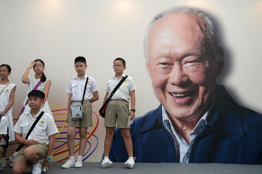 Students beside a large poster of the late Mr Lee Kuan Yew after a remembrance service held at Stamford Green on March 20.