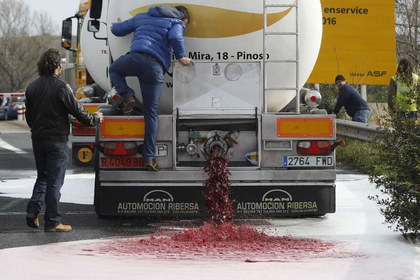 Wine flows from the tap of a Spanish truck's tanker at a toll barrier in southern France on April 4, 2016.