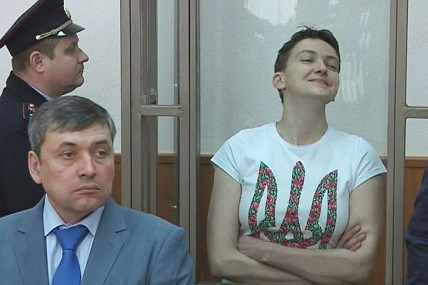 Ukrainian military pilot Nadiya Savchenko (right) looking out from a glass-walled cage during a court hearing in Donetsk, on March 22, 2016.