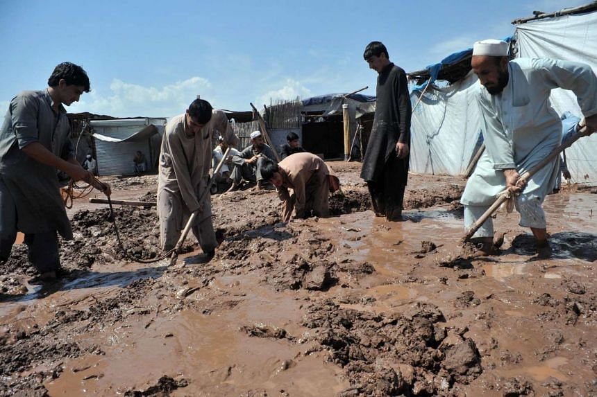Pakistani vendors remove mud from beside their shops following heavy rain on the outskirts of Peshawar on April 5, 2016.