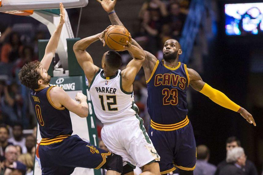 Milwaukee Bucks forward Jabari Parker (centre) shoots between Cleveland Cavaliers forwards Kevin Love (left) and LeBron James.
