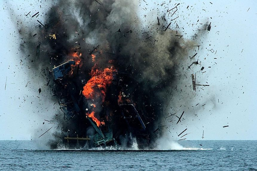 Fishing boats from Malaysia being blown up off the coast of Kuala Langsa, Aceh, yesterday. Indonesia's Maritime Affairs and Fisheries Minister has been coming down hard on poachers since taking office in 2014, ordering as many as 174 foreign boats ca