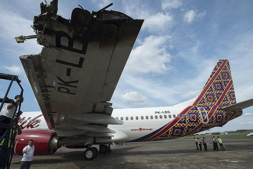Officials and investigators from the Ministry of Transportation examining the wing of a Batik Air Boeing 737-800 damaged in a collision on Monday with another plane while on the runway at Halim Perdanakusuma airport in Jakarta, Indonesia. The Transpo