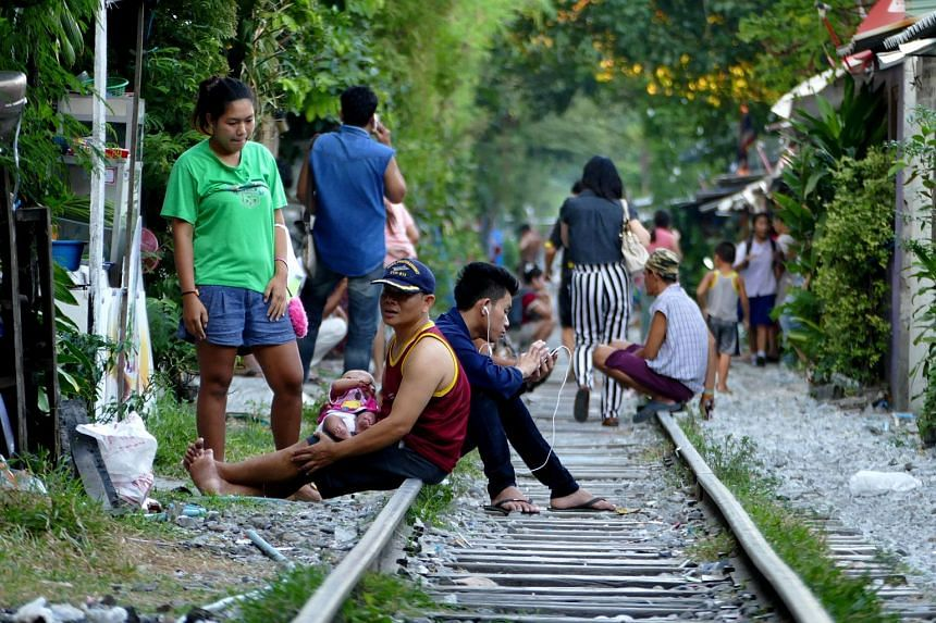 People seen at a railway track in Bangkok, Thailand.