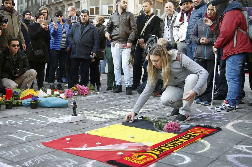 People gather around a memorial in Brussels following bomb attacks in Brussels, Belgium, March 22, 2016.
