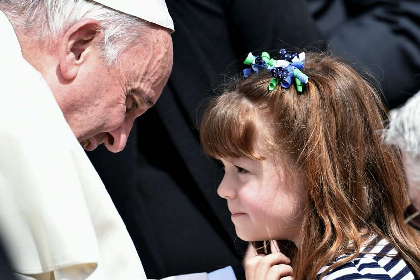 """Pope Francis speaking with five-year-old Elizabeth """"Lizzy"""" Myers at St Peter's in the Vatican, on April 6, 2016."""