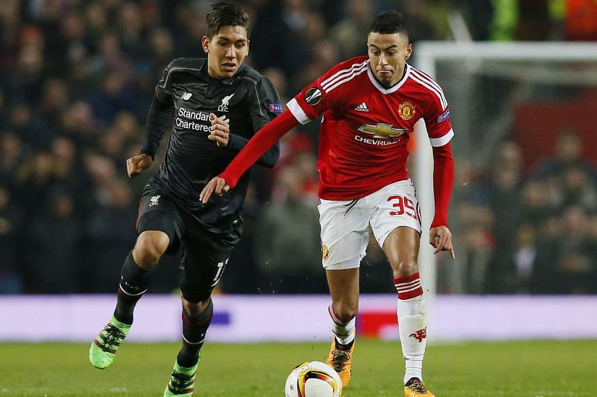 Liverpool's Roberto Firmino (left) in action with Manchester United's Jesse Lingard.