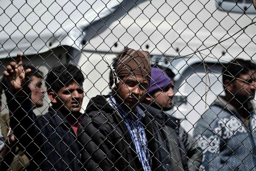 Men stand behind a chain link fence inside the Moria detention center in Mytilene on the Greek island of Lesbos on April 5, 2016.