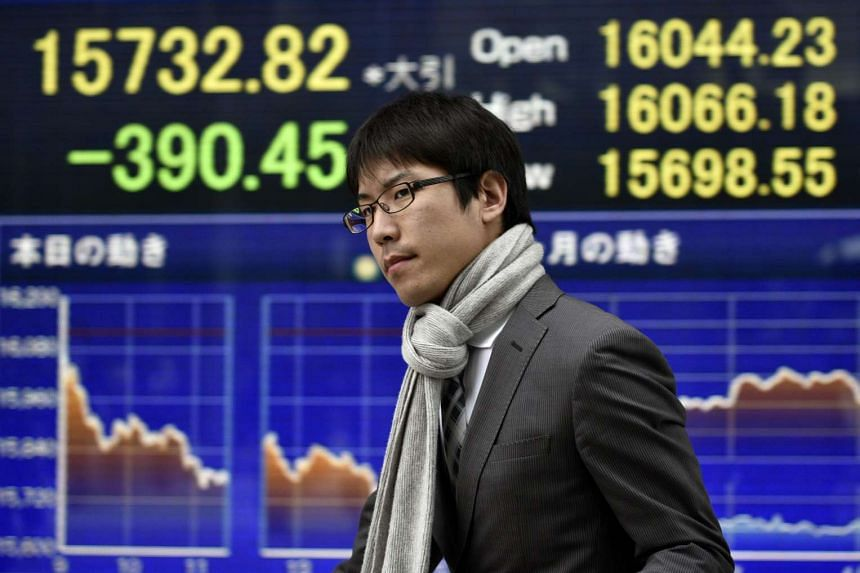 A pedestrian walking past a stock prices board in Tokyo on April 5.