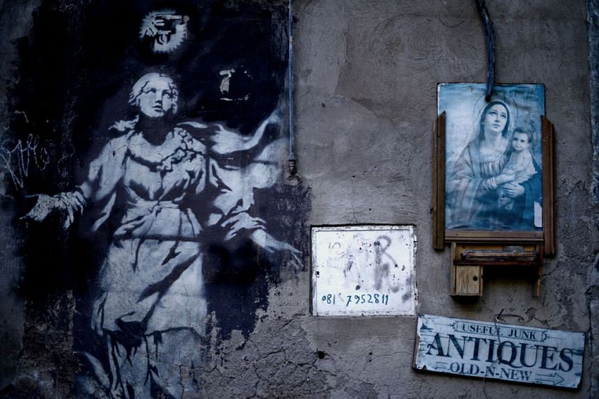 Banksy's mural (left) entitled Madonna With A Pistol in Naples has been placed under a protective cover.