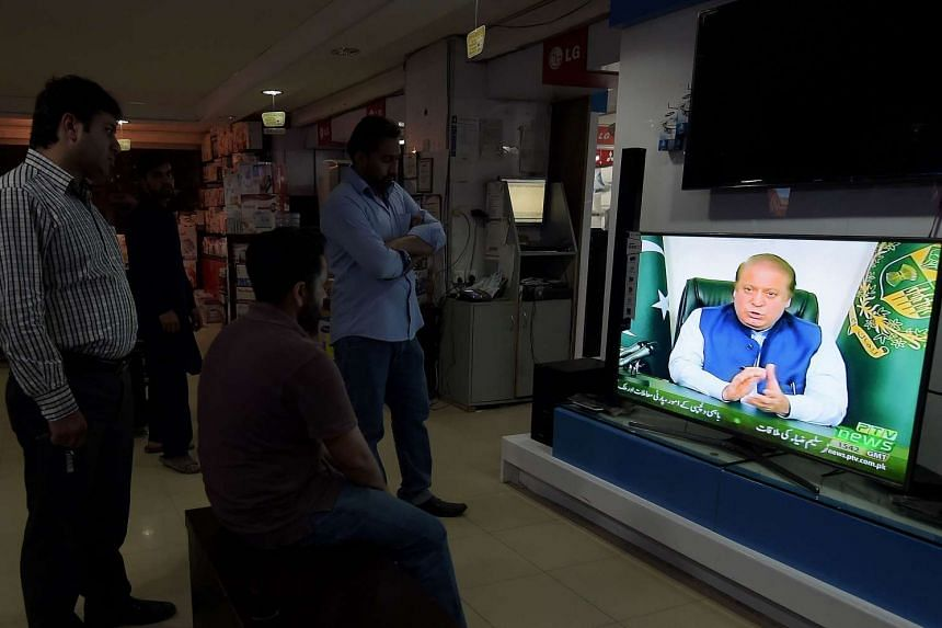 Pakistani people watch a televised addresses to the nation by Prime Minister Nawaz Sharif in Islamabad on April 5, 2016.