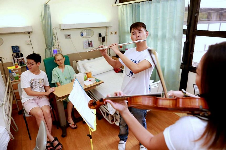 Flutist Sin Jin How and violinist Meah Tze Chuan perform classical tunes in the National University Hospital on April 6, 2016.