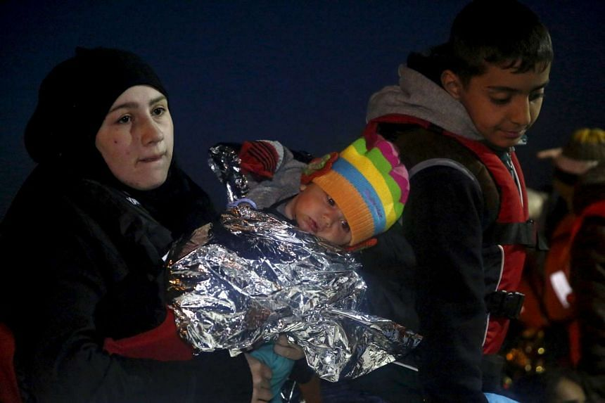 A woman holds her child as migrants arrive in Lesbos on April 3, 2016, after a rescue at sea.