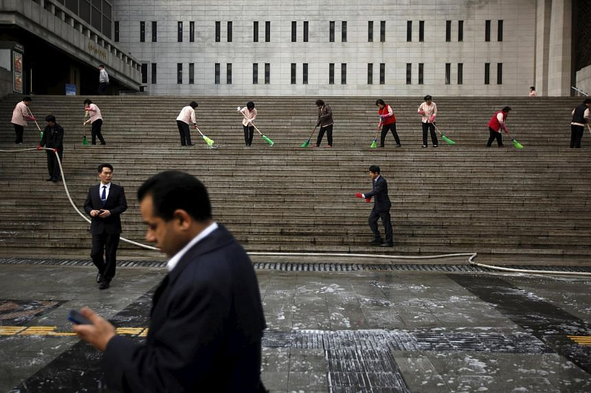 Cleaners cleaning the stairs as a man using a mobile phone walks by Sejong Centre for the Perfoming Arts in central Seoul on March 8, 2013.