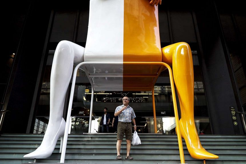 A tourist standing in front of a shopping mall in Bangkok on Jan 11.