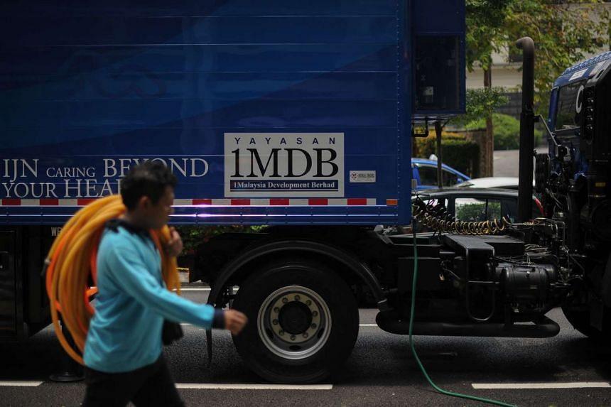 A worker walks past a poster of the 1 Malaysia Development Berhad (1MDB) logo on a truck in Kuala Lumpur on March 14, 2016.