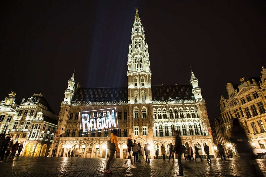 """A lighted logo reading """"I like Belgium"""" is seen on the facade of the City Hall in Brussels on March 31, 2016."""