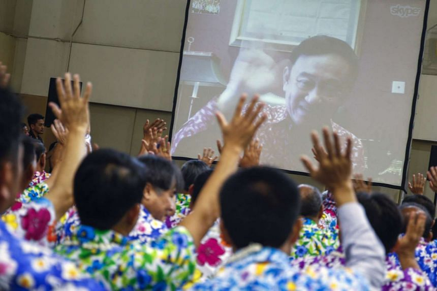 Puea Thai party members waving as former Thai prime minister Thaksin Shinawatra waves to them during a Skype video call on the occasion of Songkran festival at the party headquarters in Bangkok, Thailand, on April 7, 2016.