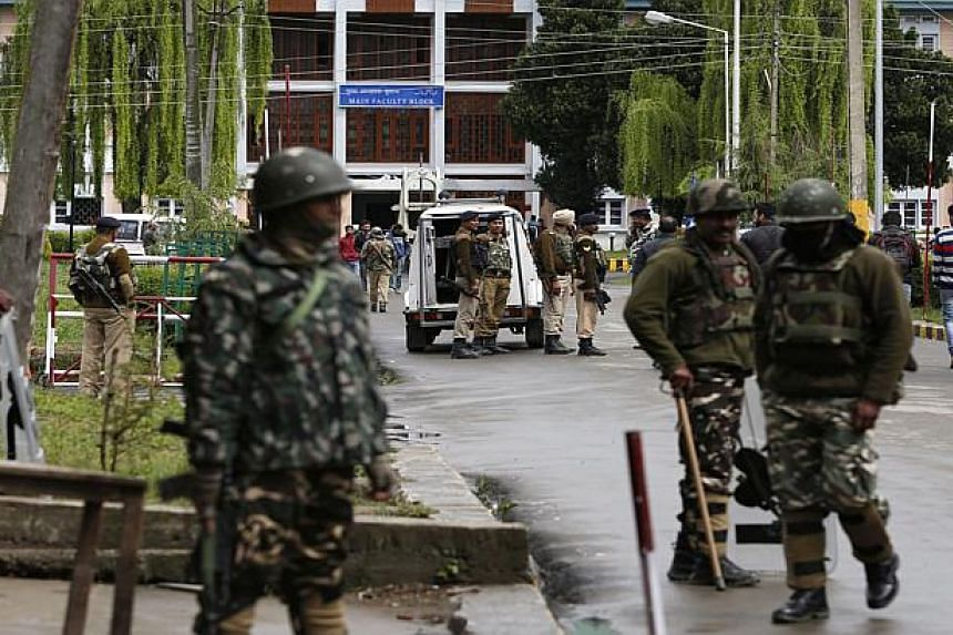 Indian paramilitary soldiers of Central Reserve Police Force stand guard near the main gate of the National Institute of Technology in Srinagar on April 6, 2016.