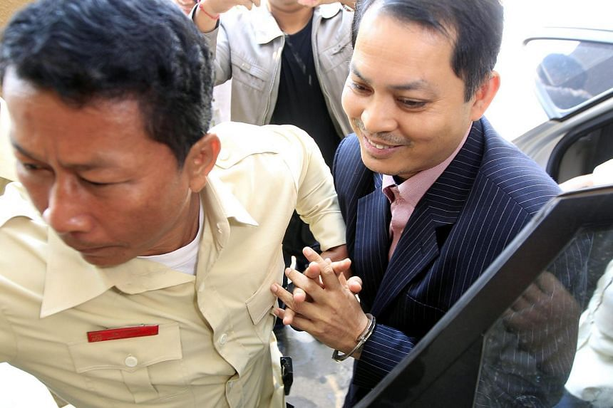 Former Cambodian Ambassador to South Korea, Suth Dina (right) is escorted by an officer, while arriving at the Municipal Court in Phnom Penh, Cambodia on April 7, 2016.