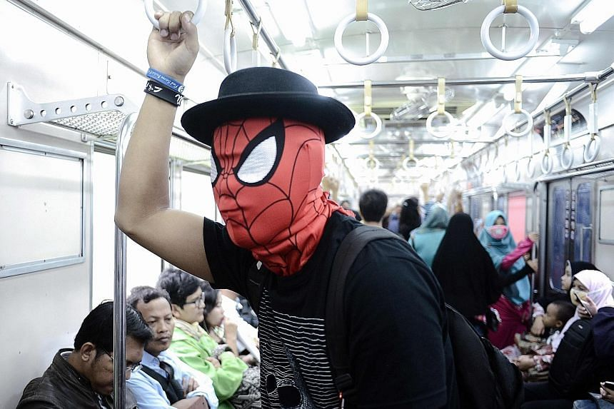 A passenger wearing a Spider-Man mask on a train in Jakarta. Wearing masks has become increasingly popular among commuters in the Indonesian capital, for health reasons due to poor air quality or to shield against foul smells - or simply as a fashion