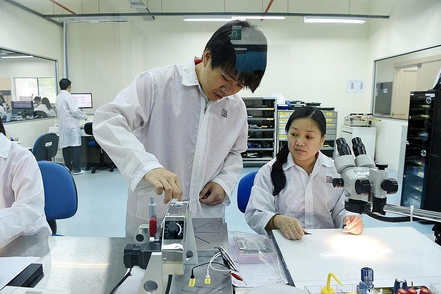 Mr Ng, seen here with test engineer Wong Yok Jung, was sent to Germany for five months' training after joining Feinmetall. On his return, he helped develop a machine to improve a process, boosting productivity by four times and cutting training time