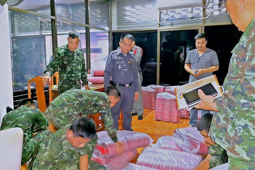 "Soldiers and police officers (above) seizing allegedly ""seditious"" water bowls (left) from the house of a former MP in Thailand's Nan province. The bowls bearing well wishes from former premier Thaksin Shinawatra were meant as gifts to supporters for"