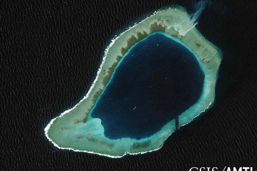 """Satellite images showing the 55m-high lighthouse (above) on Subi Reef (left), near where the US guided-missile destroyer USS Lassen sailed last October. The official Xinhua news agency said the lighthouse """"can provide efficient navigation services su"""