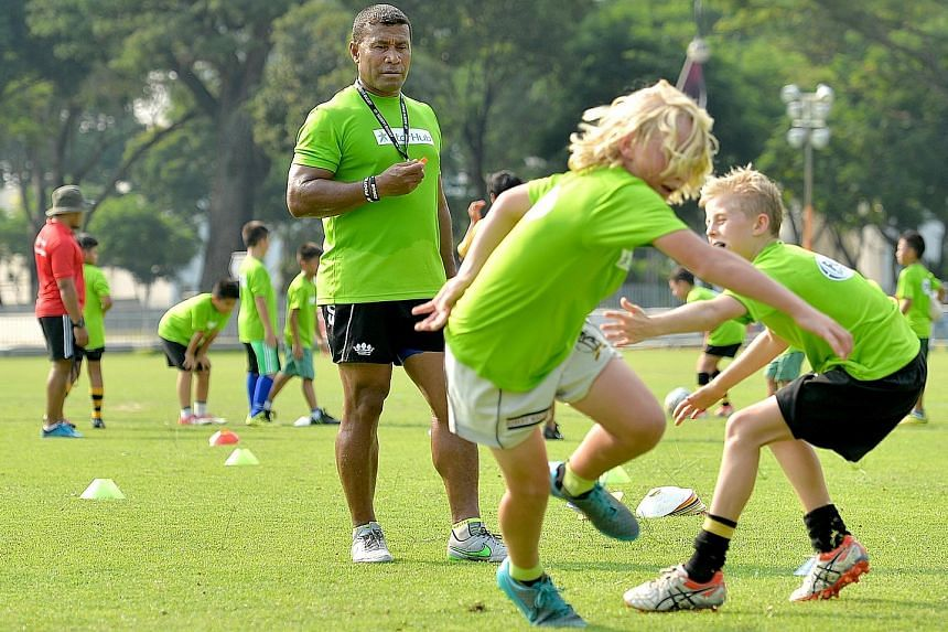 Fiji rugby sevens legend Waisale Serevi, 47, putting some of his 70 workshop participants through their paces at the Padang yesterday.