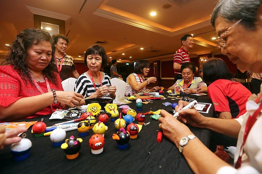 Seniors from Aljunied GRC and Hougang SMC making ornaments out of used golf balls yesterday to raise funds for wellness-related programmes in their areas.
