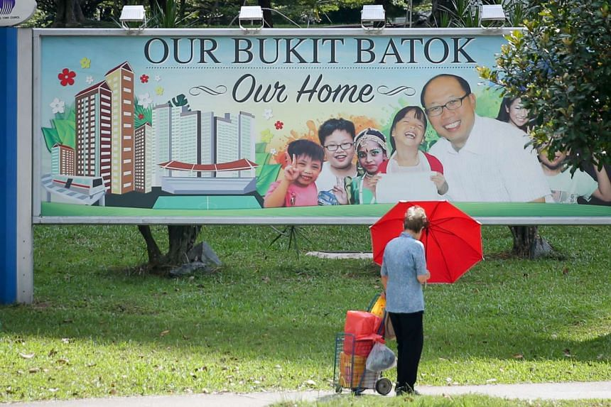A resident walking past a banner featuring former MP David Ong in Bukit Batok on March 13, 2016.