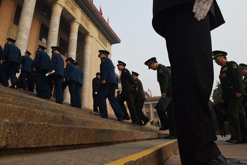 Military delegates walk up the steps of the Great Hall of the People during the National People's Congress in Beijing, on March 16, 2016.