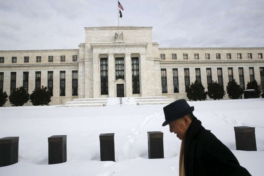 A man walks past the snow-covered grounds of the US Federal Reserve in Washington, on Jan 26, 2016.