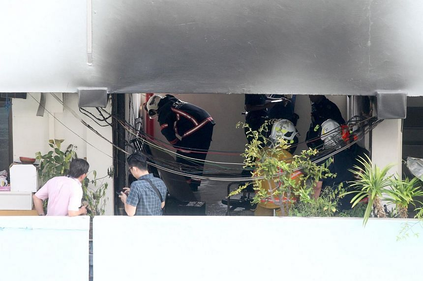 Residents and members of the Singapore Civil Defence Force outside the scene, where a fire broke out in a HDB flat in Eunos Crescent.