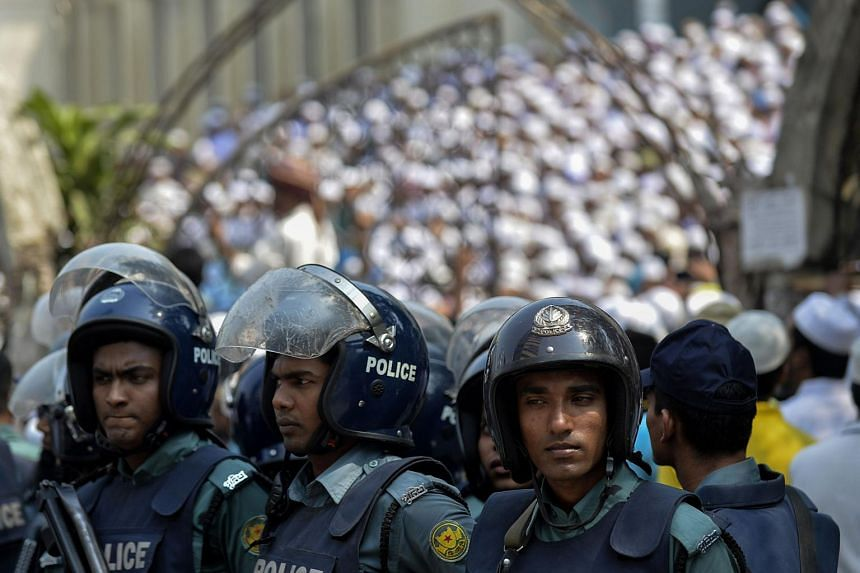 Bangladeshi police stand guard as the hardline Islamists protest outside the national mosque Baitul Mukarram in Dhaka, on March 25, 2016.