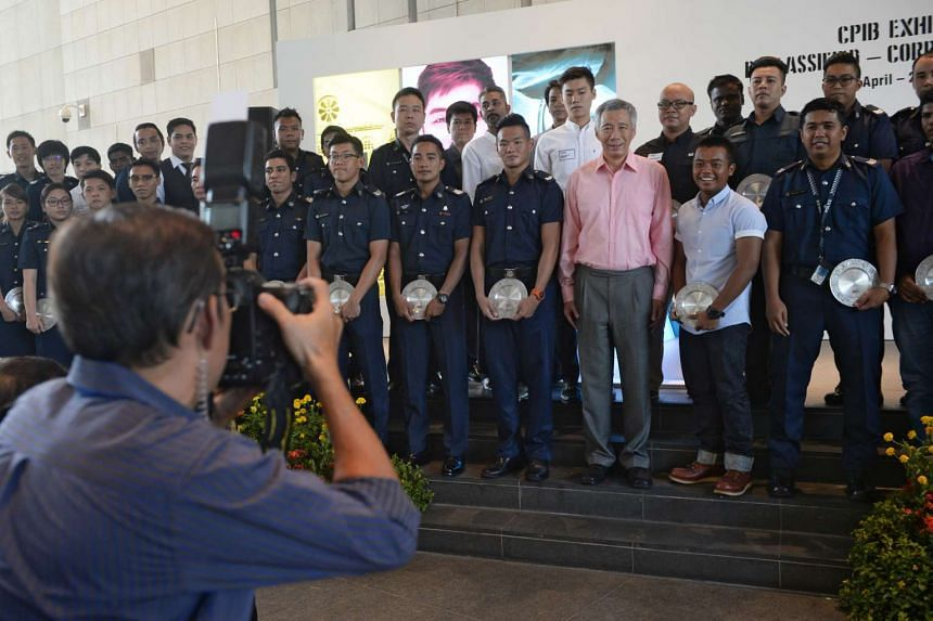 Prime Minister Lee Hsien Loong taking a group photograph with private individuals and public officers who received commendation for their acts of integrity and honesty against corruption.