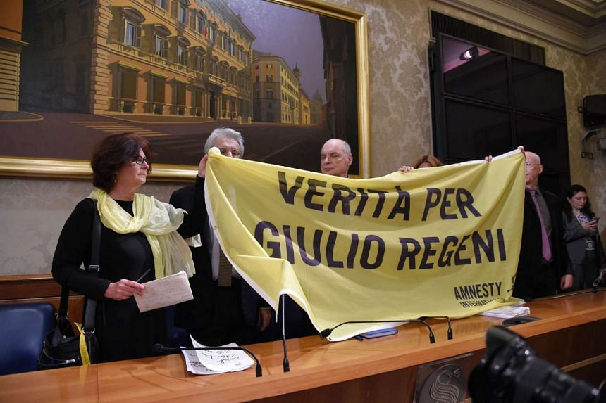 "The parents of slain Italian student Giulio Regeni holding a banner reading ""Truth for Giulio Regeni"" during a press conference in Rome on March 29, 2016."