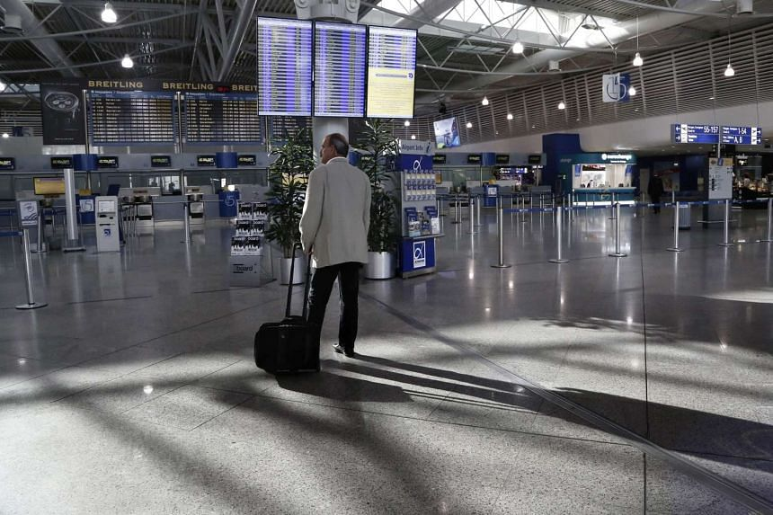 A passenger looking at a departure information board informing passengers of cancelled flights at the Eleftherios Venizelos airport in Athens on April 7, 2016.