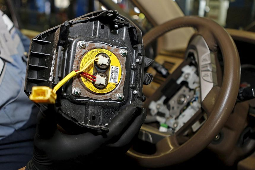 Technician Edward Bonilla holds a recalled Takata airbag inflator after he removed it from a Honda Pilot.