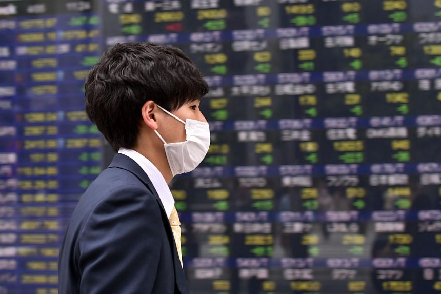 A pedestrian walks past a share prices board of the Tokyo Stock Exchange in Tokyo on April 5, 2016.