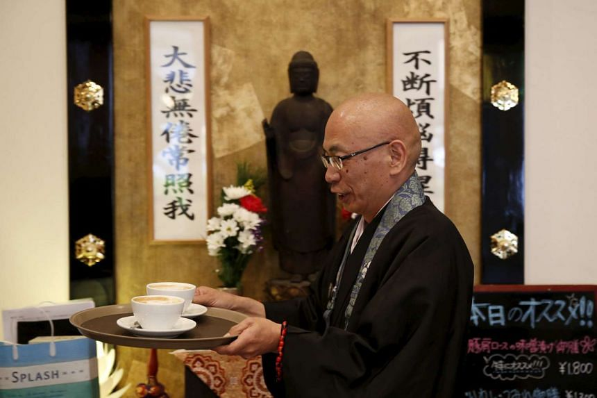 Buddhist monk and one of the on-site priests Shokyo Miura, carrying cups of coffee past a statue of Buddha at Tera Cafe in Tokyo, Japan, on April 1, 2016.
