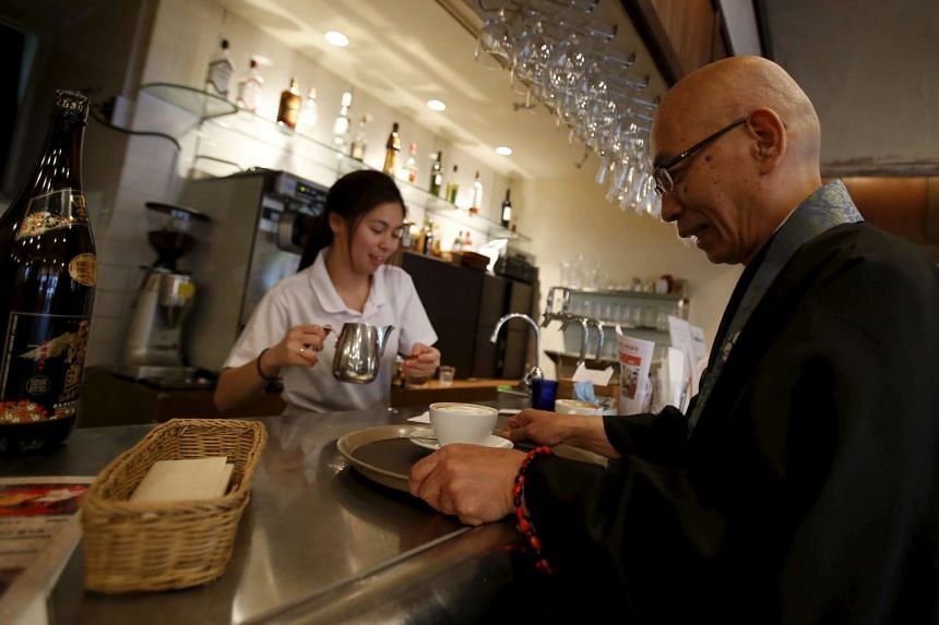 Buddhist monk and one of the on-site priests Shokyo Miura, carrying a cup of coffee in front of a bar counter at Tera Cafe in Tokyo, Japan, on April 1, 2016.
