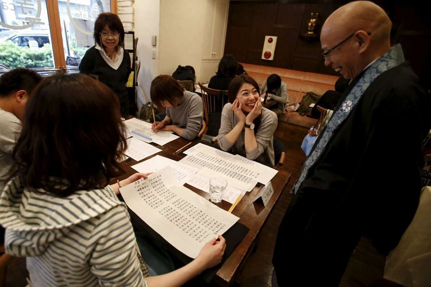 A woman speaks to Buddhist monk and one of the on-site priests Shokyo Miura, after tracing Buddhist sutras at Tera Cafe in Tokyo, Japan, on April 1, 2016.