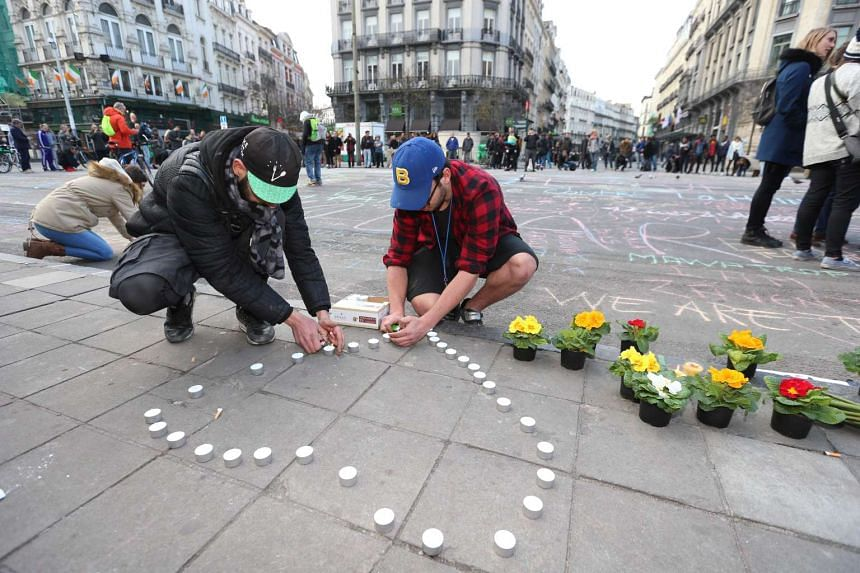 People leave candles and flowers in tribute to victims of the bomb attacks in Brussels on March 22, 2016.